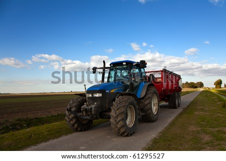 Tractor on the road with trailer - stock photo