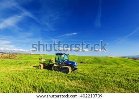 Tractor on tracks in the summer sunny day on a green field. - stock photo