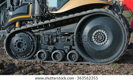 tractor outside with rubber crampons - stock photo