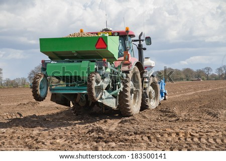 Tractor planting potatoes in rural Shropshire, UK.