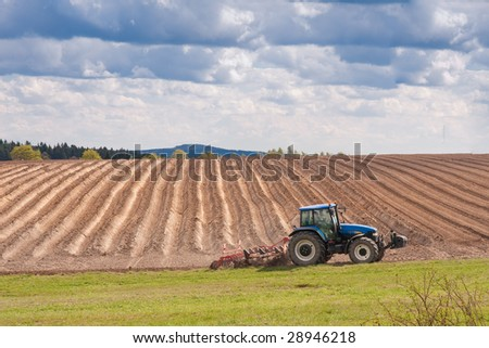 tractor planting potatoes in the springtime
