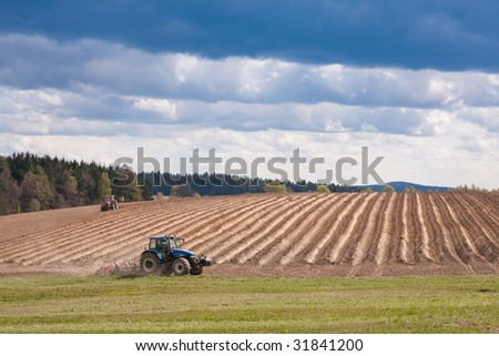 tractor planting potatoes in the springtime - stock photo