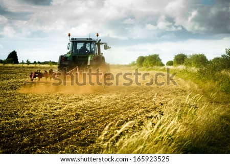 Tractor ploughing a field with a trail of dust behind it.  - stock photo