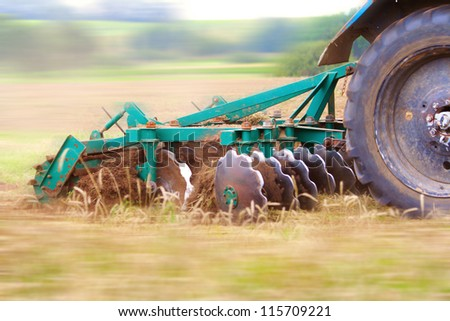 Tractor ploughing up the field. Motion blur was done for effect to emphasize speed - stock photo