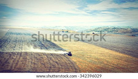 Tractor plowing a field - stock photo