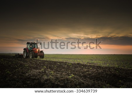 Tractor plowing a field at dusk - stock photo