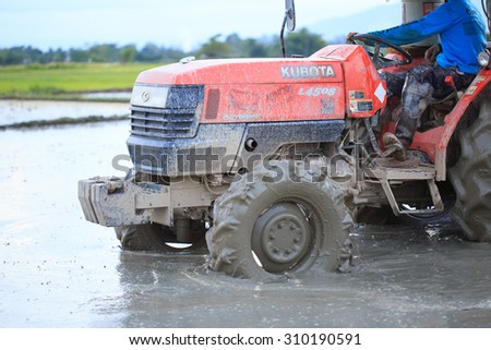 Tractor plowing a rice field in Chiang Mai, Thailand on August 07, 2015. - stock photo