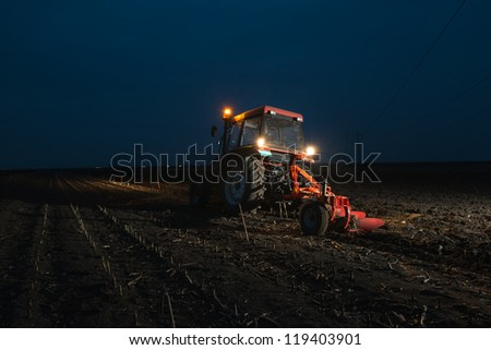 Tractor plowing at night - stock photo