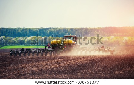 Tractor plowing farm field in preparation for spring planting. - stock photo