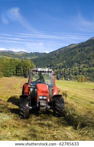 Tractor plowing field on a sunny autumn day. - stock photo