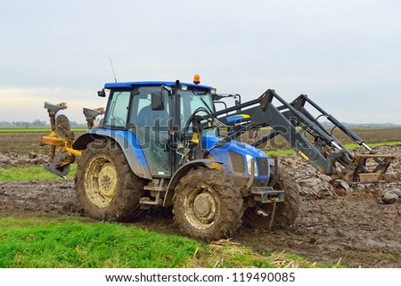 tractor plowing muddy farmland