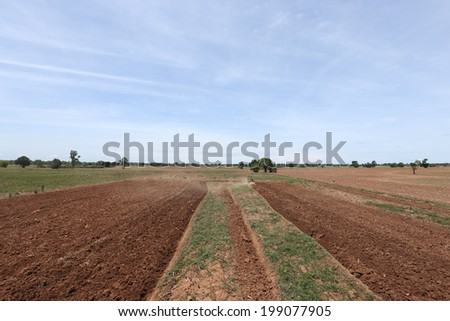 tractor plowing soil for agriculture work - stock photo