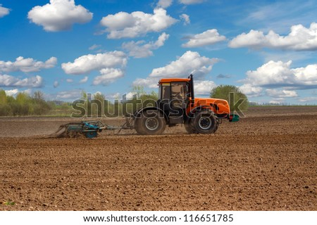 Tractor plowing the field - stock photo