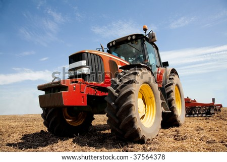 Tractor plowing the field in autumn. General farming activity. Wide angle shot on horizontal - stock photo