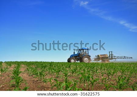Tractor plowing the fields horizontal - stock photo