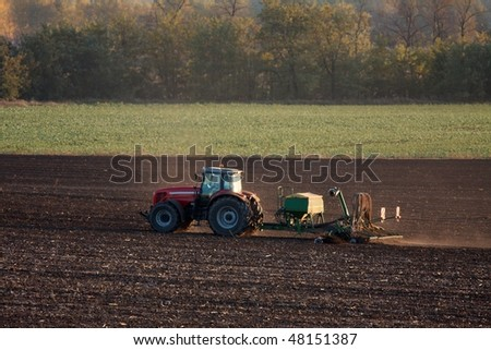 Tractor plowing the soil - stock photo