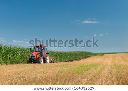 Tractor plowing the stubble field - stock photo