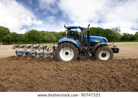Tractor plows field at high speed.