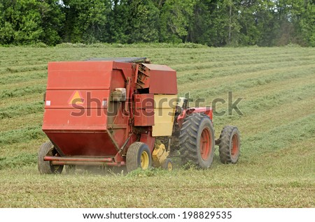 Tractor pulling a large round baler to pick up high value alfalfa grass feed from a summer field in Oregon