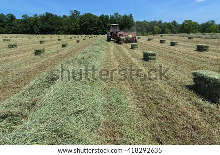 Tractor Pulling Baler to Make Fresh Hay Bales - stock photo