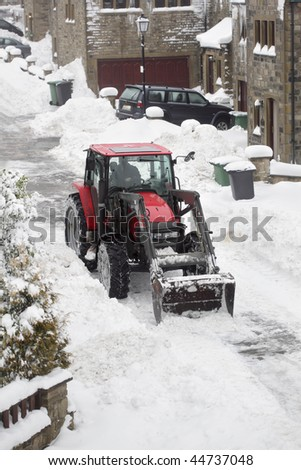 Tractor removing snow from a residential housing estate in winter - stock photo