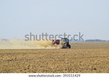 Tractor rides on the field and makes the fertilizer into the soil. Clouds of dust from the dry soil tractor trailer. Fertilizers after plowing the field. - stock photo
