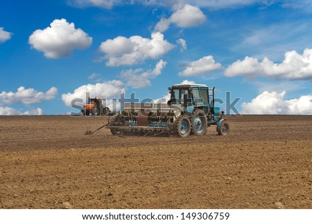 Tractor sowing the field with the seeder - stock photo