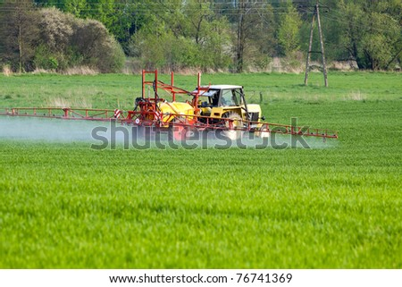 Tractor spraying a crop field on farm - stock photo