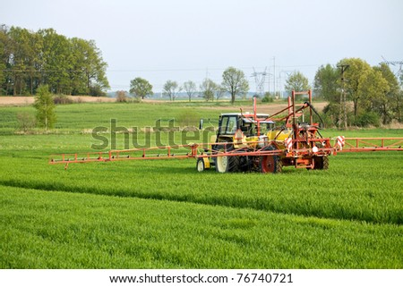Tractor spraying a field on farm - stock photo