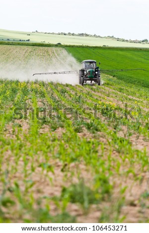 Tractor spraying a field on farm in spring, agriculture - stock photo