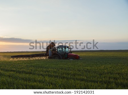 Tractor spraying crops at sunset on rural field - stock photo