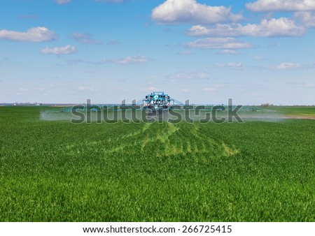 tractor spraying pesticides - stock photo