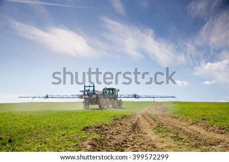 Tractor spraying pesticides on green spring bean - stock photo