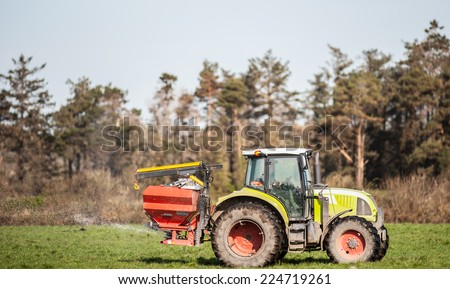 Tractor spraying rural farm field  - stock photo