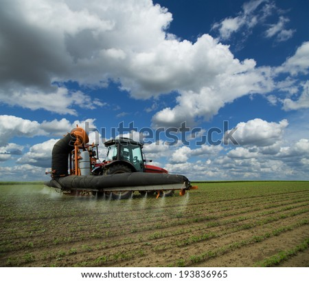 Tractor spraying soybean crops field at spring season, herbicides, pesticides - stock photo