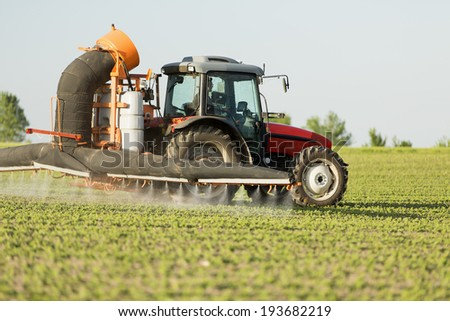 Tractor spraying soybean crops field with sprayer, pesticides and herbicides - stock photo