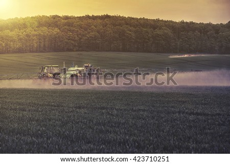 Tractor spraying soybean field at spring - stock photo