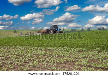 Tractor spraying the field on a sunny day - stock photo