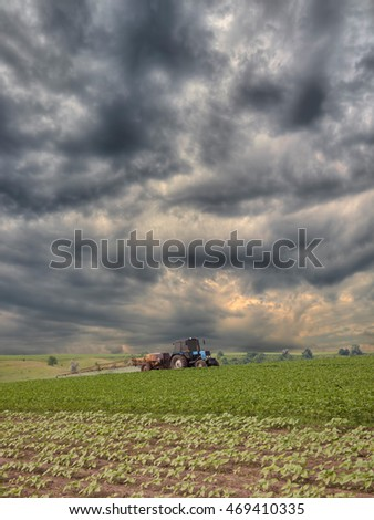 Tractor spraying the field with a stormy sky on the background