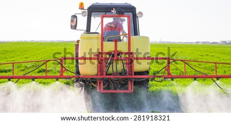 Tractor spraying wheat field with sprayer - stock photo