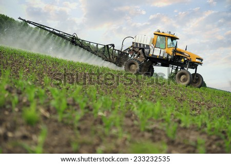 Tractor sprinkling young plants from pests - stock photo