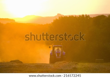 Tractor straw baling in sunny, rural field - stock photo