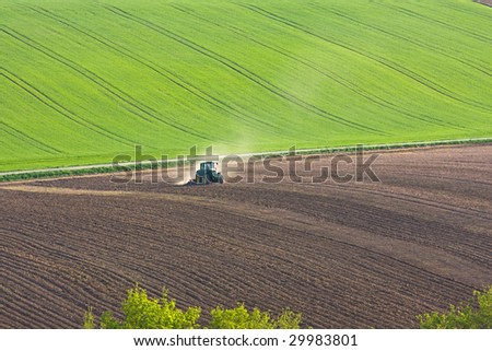 tractor throwing up dust on farmland - stock photo