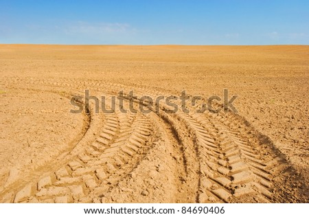 tractor track on empty fallow field