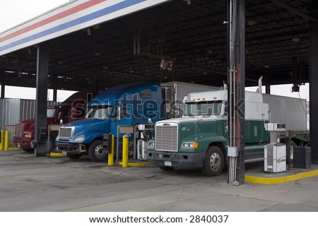 Tractor trailer rigs parked at truck stop for servicing - stock photo