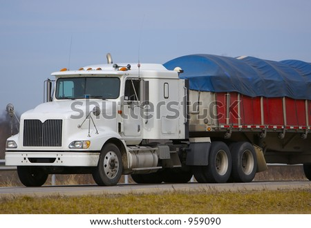 Tractor Trailer with Tarp Covering Load.  Blue Sky in Background - stock photo