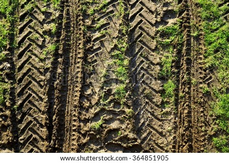 Tractor tyre print on a wet soil in field - stock photo
