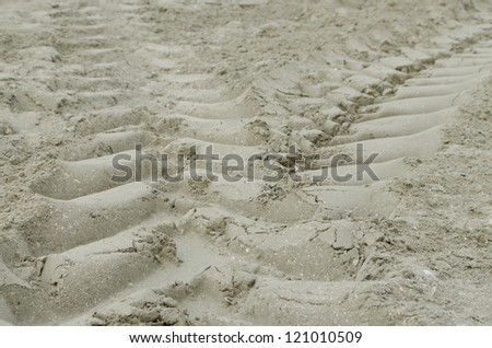 Tractor wheel tracks in the beach sand - stock photo