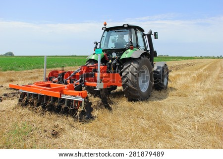Tractor with a disc harrow on the farmland - stock photo