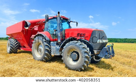 Tractor with a tank for transporting grain - stock photo